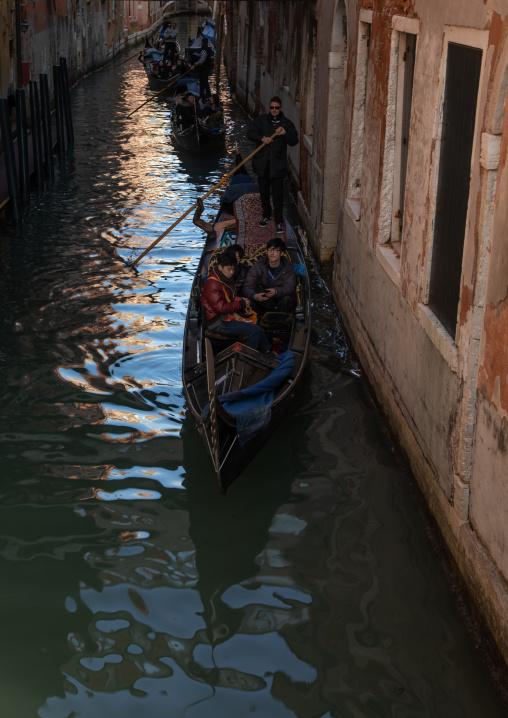 Tourists riding in godolas in a small canal, Veneto, Venice, Italia