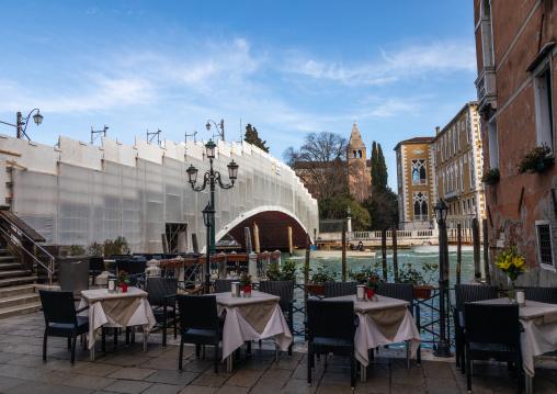 Empty restaurant in front of a scaffolding on a bridge, Veneto, Venice, Italia