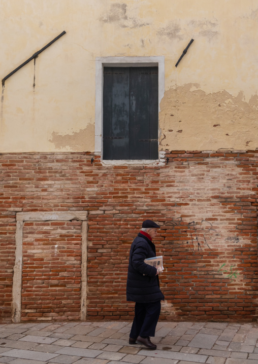 An italian man walks past old house, Veneto, Venice, Italia