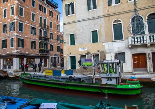 Boat collecting garbage in the canal, Veneto, Venice, Italia