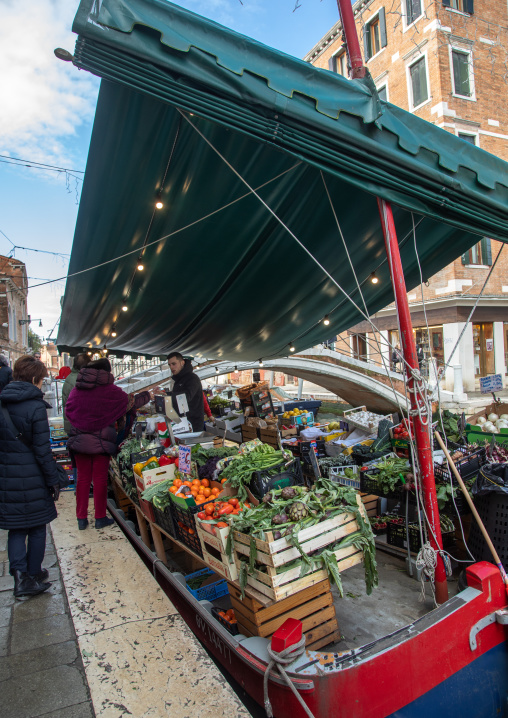 Market trader is selling fruits and vegetables at rialto market, Veneto, Venice, Italia