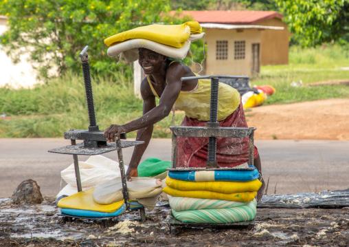 African woman putting attiéké in bags, Région des Lacs, Sakiare, Ivory Coast