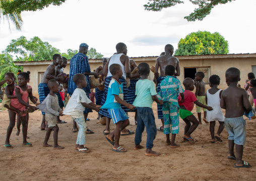 Musicians performing and children dancing during a Goli sacred mask dance in Baule tribe, Région des Lacs, Bomizanbo, Ivory Coast