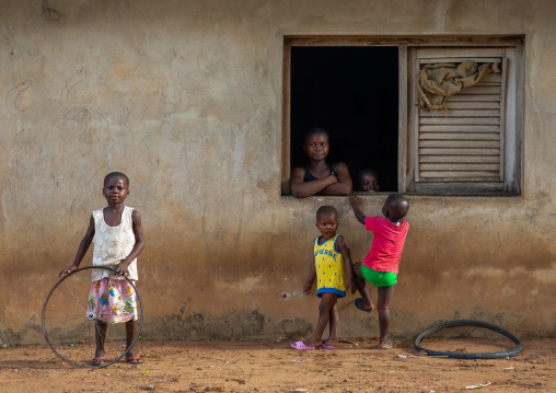 African mother looking thru her window house her children playing, Région des Lacs, Bomizanbo, Ivory Coast
