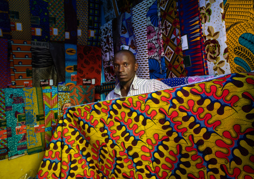 African seller with colorful african fabrics in a shop, Comoé, Abengourou, Ivory Coast