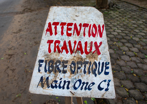Warning billboard in the street about a  construction site for internet optic fiber, Sud-Comoé, Grand-Bassam, Ivory Coast