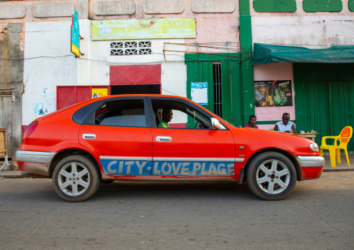 Red taxi with the slogan city love plage on the car, Sud-Comoé, Grand-Bassam, Ivory Coast