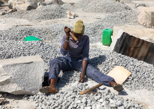 African woman crashing stones in a granite quarry, Savanes district, Shienlow, Ivory Coast