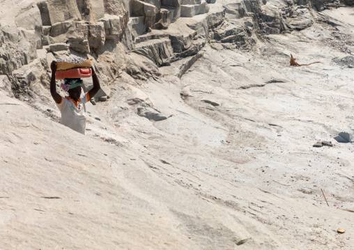 African woman carrying stones in a granite quarry, Savanes district, Shienlow, Ivory Coast