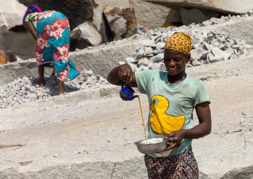 African woman preparing tea in a granite quarry, Savanes district, Shienlow, Ivory Coast
