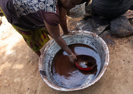 Senufo woman prepairing shea butter in a traditional karité factory, Savanes district, Tcheregnimin, Ivory Coast