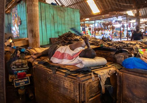 African man sleeping on a market stall during Ramadan, Poro region, Korhogo, Ivory Coast