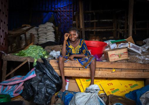 African girl sit in a market stall, Poro region, Korhogo, Ivory Coast