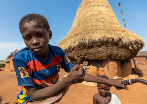 African boy in front of a Senufo fetish house whose roof gets a new layer every year, Savanes district, Niofoin, Ivory Coast