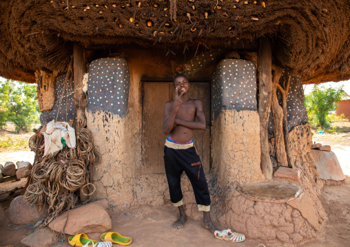 African man standing at the entrance of a Senufo fetish house, Savanes district, Niofoin, Ivory Coast
