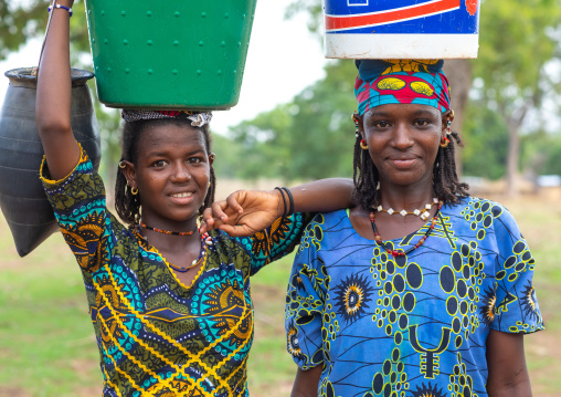 Portrait of Peul tribe girls carrying buckets full of water on the head, Savanes district, Boundiali, Ivory Coast