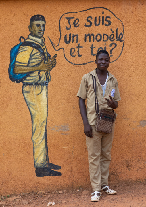 African boy standing in front of a mural depicting a pupil who works well at school, Savanes district, Boundiali, Ivory Coast