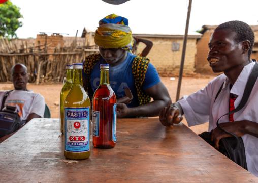 Senufo young men drinking pastis during the poro society age-grade initiation, Savanes district, Ndara, Ivory Coast