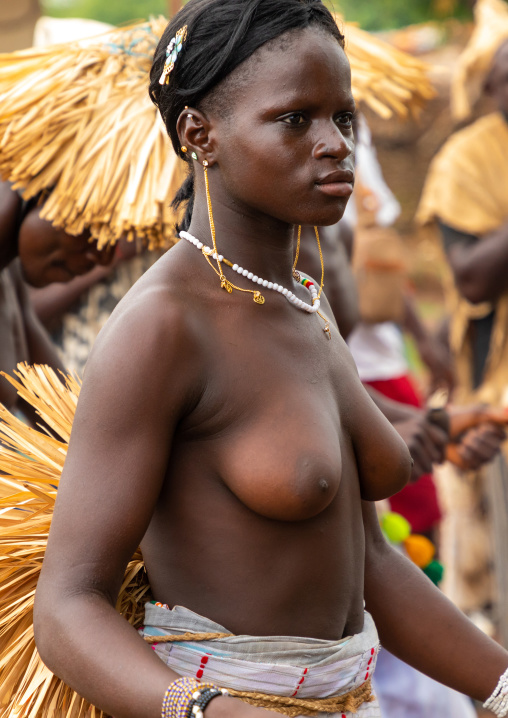 Young Senufo shirtless woman dancing the Ngoro during a ceremony, Savanes district, Ndara, Ivory Coast