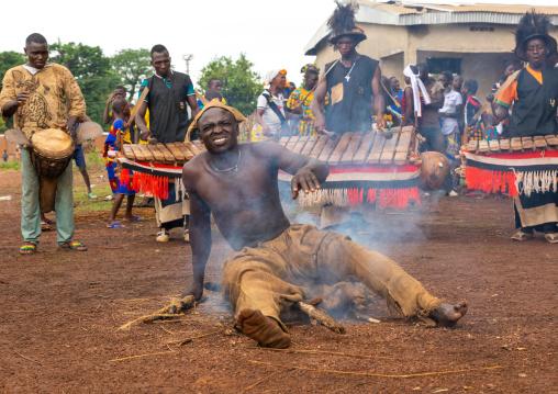 Shirtless man sitting in the fire during the Ngoro dance, Savanes district, Ndara, Ivory Coast