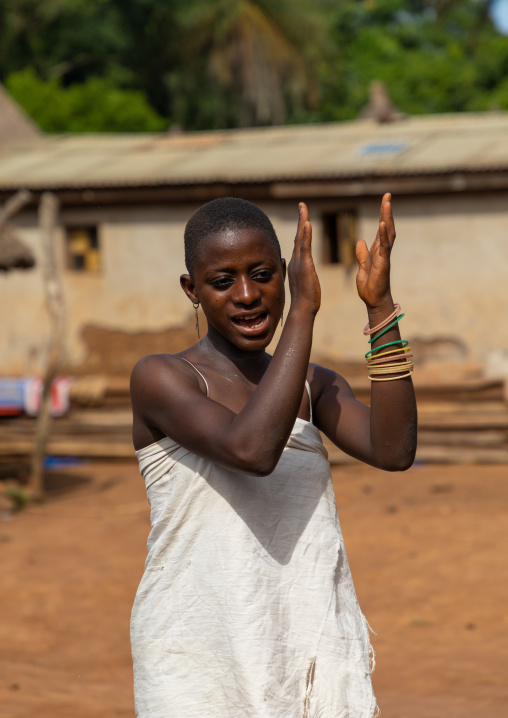 Dan tribe young woman clapping hands and dancing during a ceremony, Bafing, Gboni, Ivory Coast