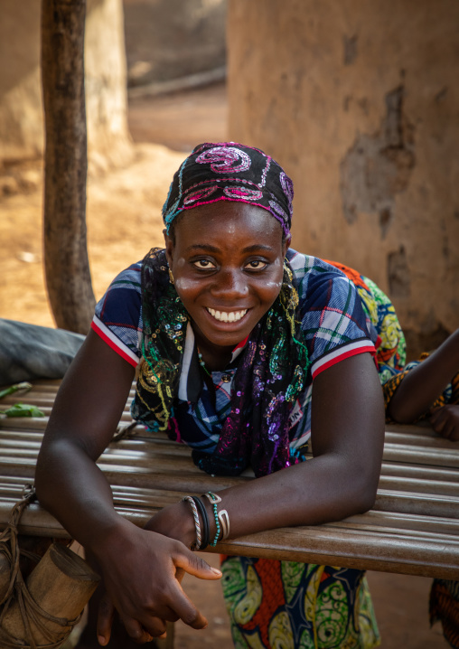 Portrait of a Dan tribe smiling woman resting on a wood bed, Bafing, Gboni, Ivory Coast