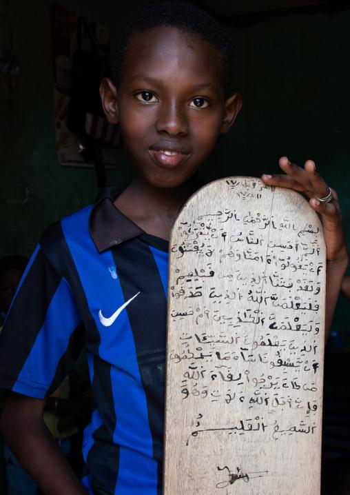 Boy with a wood board for writing koran in a coranic school, Tonkpi Region, Man, Ivory Coast