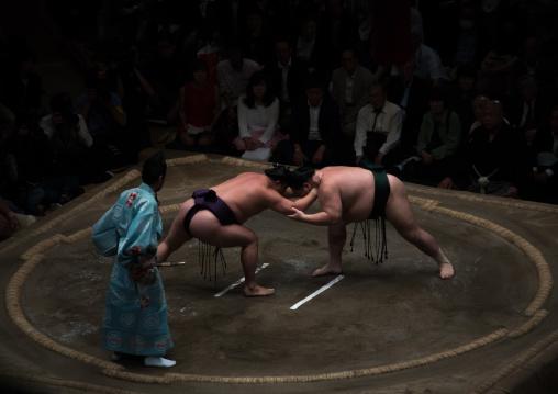 Two sumo wrestlers fighting at the ryogoku kokugikan arena, Kanto region, Tokyo, Japan