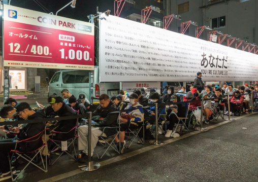 People queueing and sleeping in the street for the opening of a new shop, Kanto region, Tokyo, Japan