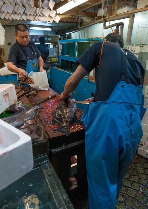 Vendor slicing fish at the tsukiji fish market, Kanto region, Tokyo, Japan