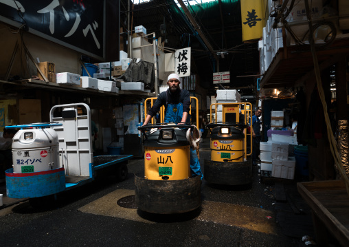 A man driving a motorized cargo cart called a taretto, Kanto region, Tokyo, Japan