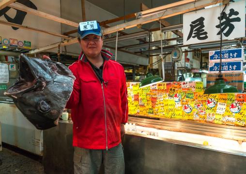 Vendor holding a big tuna fish in tsukiji fish market, Kanto region, Tokyo, Japan