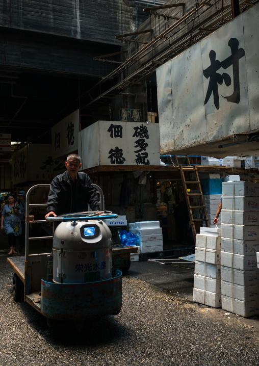 A man driving a motorized cargo cart called a taretto, Kanto region, Tokyo, Japan