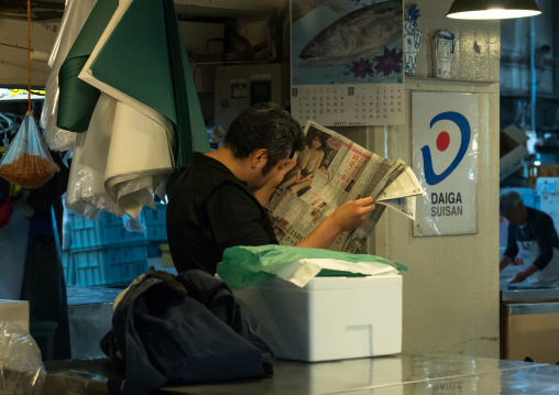Vendor reading a newspaper in tsukiji fish market, Kanto region, Tokyo, Japan