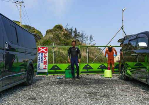 Japanese surfer in the contaminated area in front of a authorized entry prohibited sign
