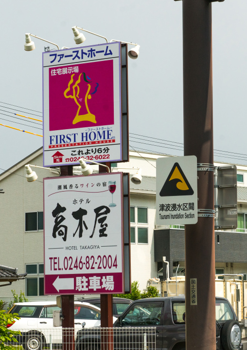 A sign on a coastal road warns people about tsunami bewtweens hotel and real estate ads, Fukushima prefecture, Tairatoyoma beach, Japan