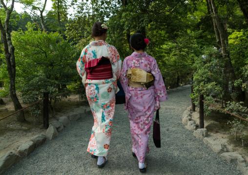 Chinese tourist women wearing geisha kimonos in a zen garden, Kansai region, Kyoto, Japan