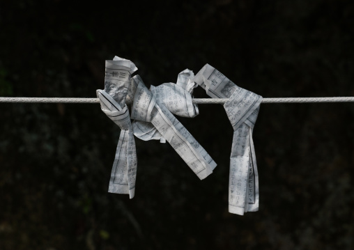 Folded paper fortunes tied to wires on a board, Kansai region, Kyoto, Japan