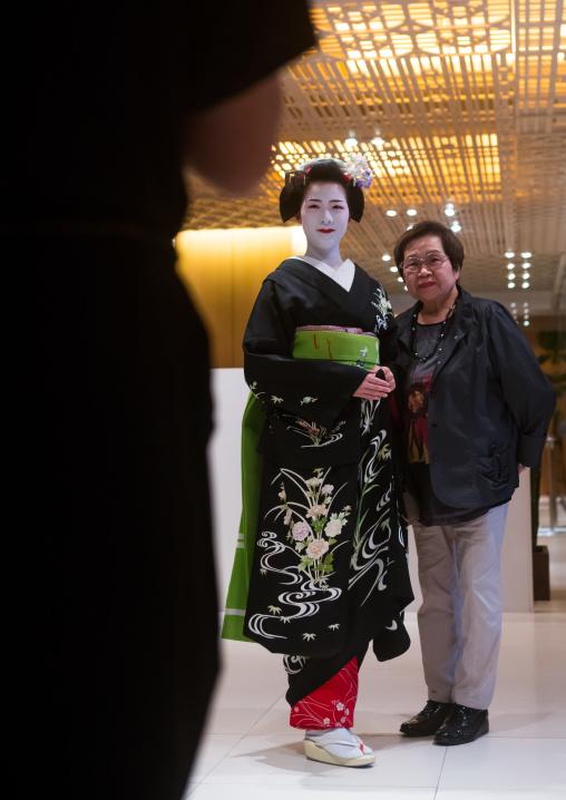 Maiko in hayatt hotel hall posing for tourists, Kansai region, Kyoto, Japan