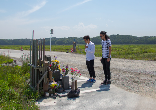 Japanese men praying in front of a shrine to victims of the 2011 tsunami five years after, Fukushima prefecture, Namie, Japan