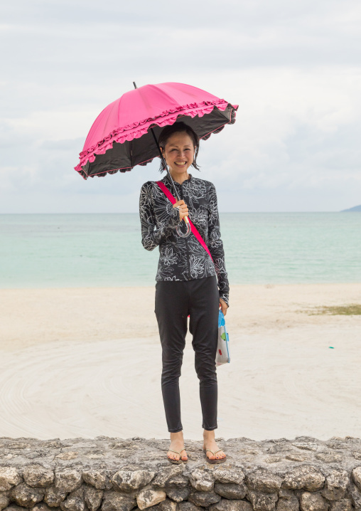 Japanese woman with an umbrella in kondoi beach, Yaeyama Islands, Taketomi island, Japan