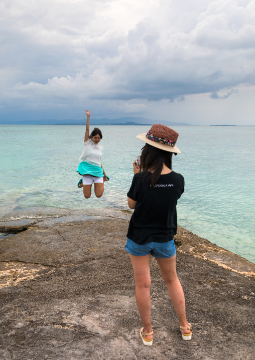 Japanese tourist jumping for a picture on nishi pier, Yaeyama Islands, Taketomi island, Japan