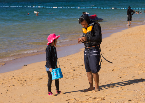 Japanese tourists with high protection against the sun in sunset beach, Yaeyama Islands, Ishigaki, Japan