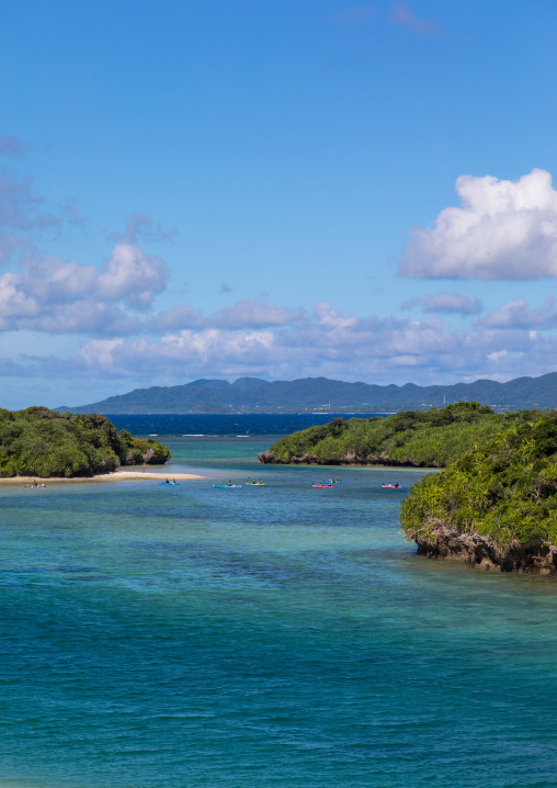 Tropical lagoon with clear blue water surrounded by lush greenery in Kabira bay, Yaeyama Islands, Ishigaki, Japan