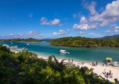 Glass bottom boats in the tropical lagoon beach with clear blue water and white sand in Kabira bay, Yaeyama Islands, Ishigaki, Japan