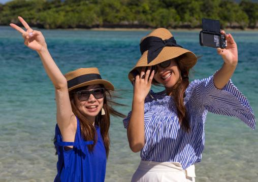 Japanese girls taking selfie in the tropical lagoon with clear blue water in Kabira bay, Yaeyama Islands, Ishigaki, Japan
