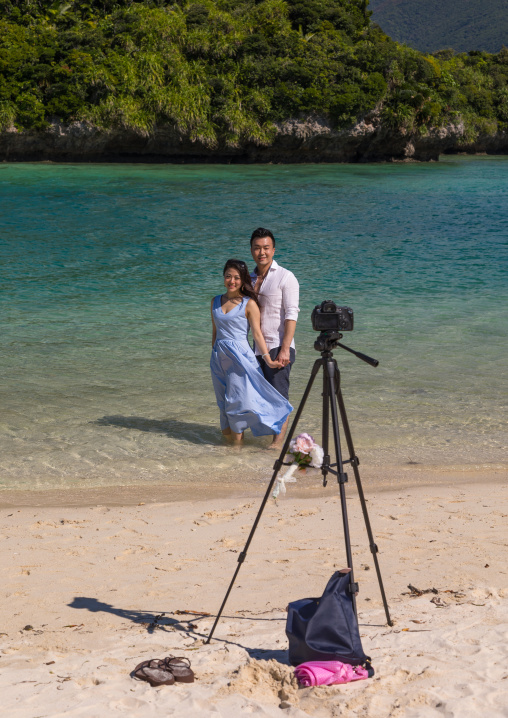 Japanese couple posing in the tropical lagoon with clear blue water in Kabira bay, Yaeyama Islands, Ishigaki, Japan