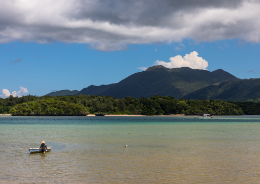 Japanese fisherman in tropical lagoon with clear blue water in Kabira bay, Yaeyama Islands, Ishigaki, Japan