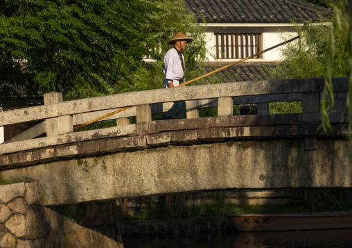 Japanese man in traditional clothing crossing a bridge, Okayama Prefecture, Kurashiki, Japan