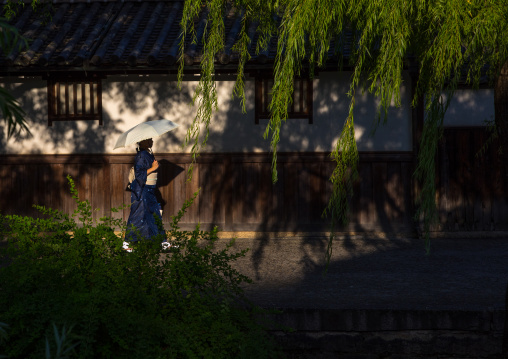 Japanese woman with an umbrella passing in front old houses along the riverbank, Okayama Prefecture, Kurashiki, Japan